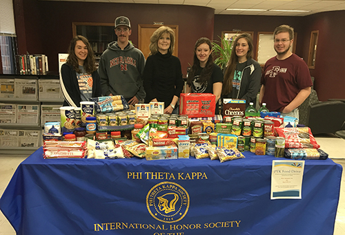 The Phi Theta Kappa group standing with all the food they've collected in their food drive displayed on a table in front of them.