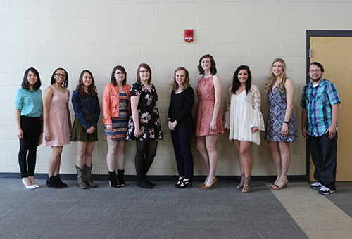 Several of the students in Phi Theta Kappa posing in front of a wall.