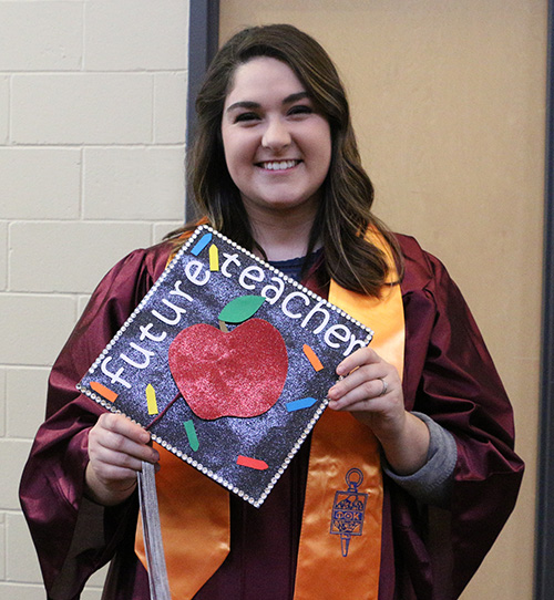 "A young female student, in her graduation robe, smiling and displaying the top of her hat, which has a paper cutout of an apple and the words ""Future Teacher"" on it."