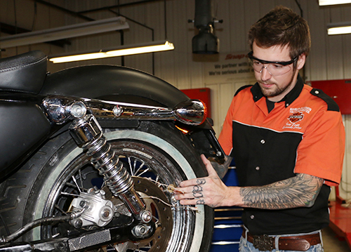 A Harley-Davidson student examining the back tire of a motorcycle.