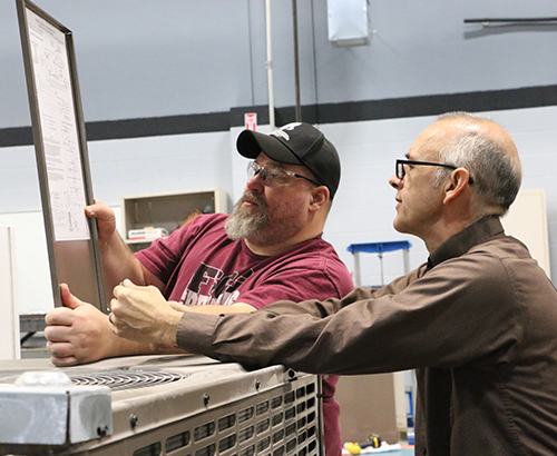 Two HVAC instructors leaning against an air conditioner while reviewing instructions.