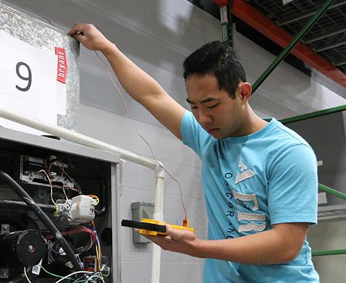 An HVAC student using a diagnostics device to check voltage.