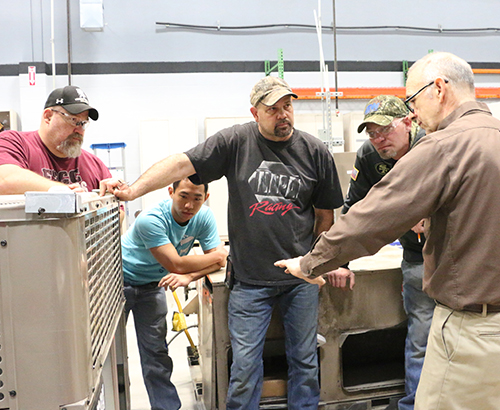 An HVAC instructor describing something to a few students.