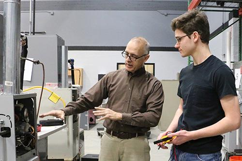 A teacher showing a student the inside of a machine in HVAC class.