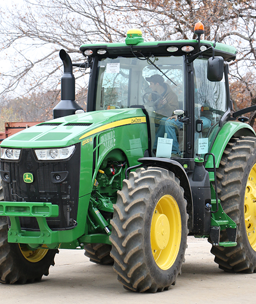 A student driving a John Deere tractor.