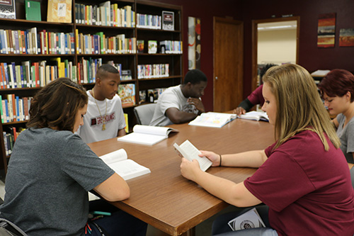Several students gathered around a table in the library, studying together.