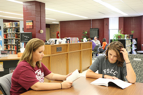 Two students reading books at a table in the library.