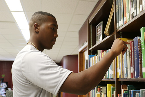 A student about to pick a book from a bookshelf.