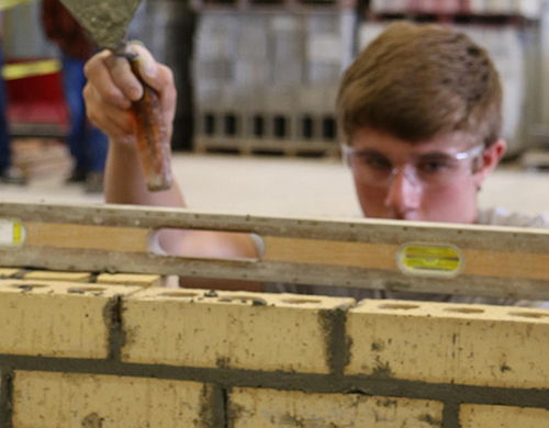 A Masonry student measuring the angle of a wall to confirm it is level.