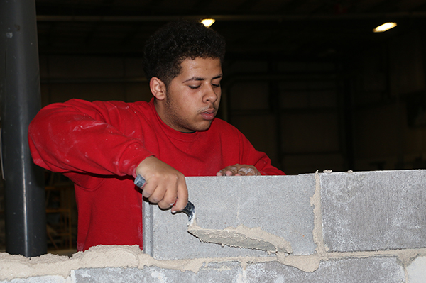A masonry student applying mortar to the bricks of his wall to keep them together.