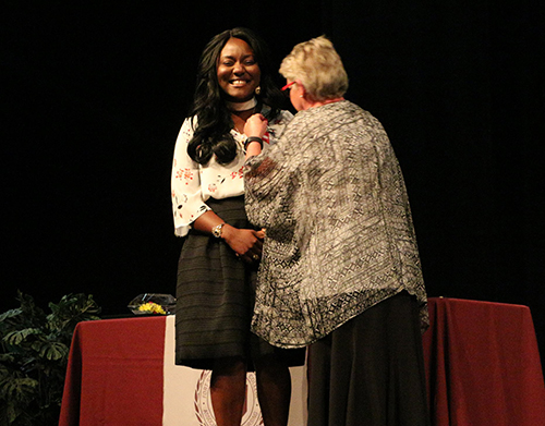 A nursing student ecstatically accepting a pin at a Nurse Pinning Ceremony.