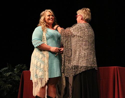 A nursing student happily accepting a pin at a Nurse Pinning Ceremony.