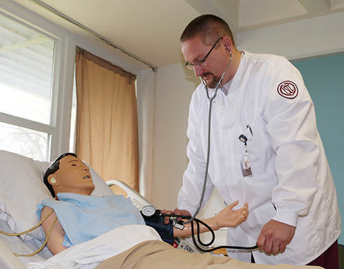 A nursing student taking the blood pressure of a dummy patient.
