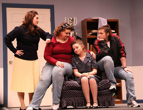 Four of the student actresses in the Odd Couple play. One looking depressed in a chair with two sitting on the chair's arms, offering her comfort, while the fourth actress stands nearby.