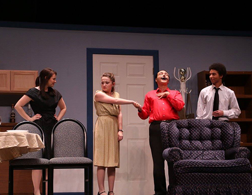 Four of the student actors and actresses for the Odd Couple play. One actress with a disgusted look on her face is having her hand held by one of the actors while he laughs. The other actor and actress look on from the sides.