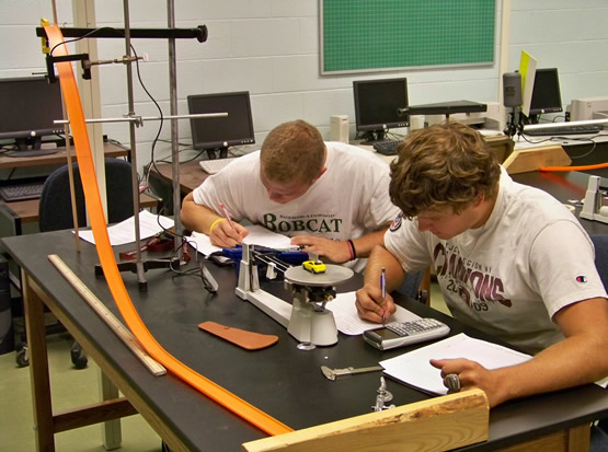 Two students writing down notes after conducting a physics experiment with toys cars and gravity.