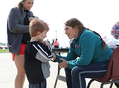 A nursing student cheerfully showing a young boy how to use a stethoscope.