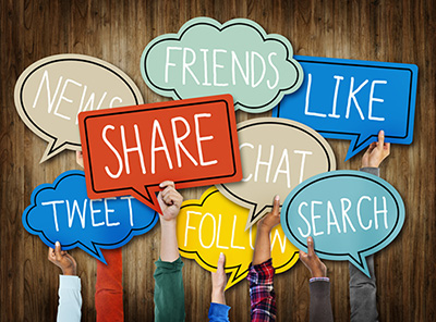 "Several hands holding up signs that display common words used in social media, such as ""Friends"", ""News"", and ""Share""."