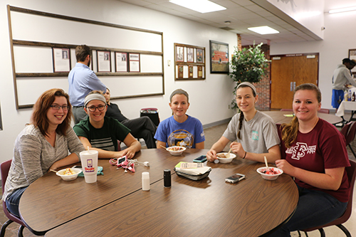 Five female students sitting at a table in the cafeteria and enjoying some ice cream.