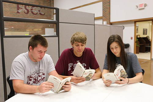 Three students sitting at a table, reading books in the Student Union.
