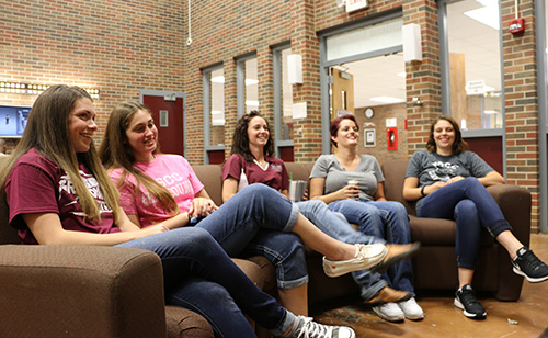 Five students sitting together on a couch in the Student Union, watching television.