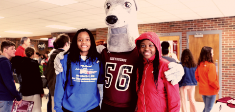 two students posing with the greyhound mascot during a business expo