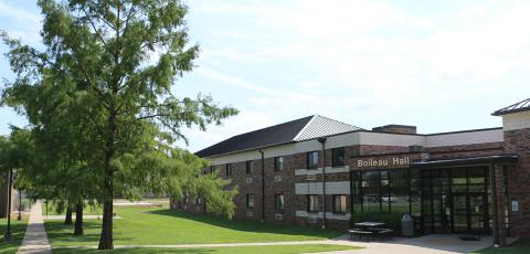 An open view of Boileau Hall's entrance to the right and a line of trees leading to the back of Arnold Area on the left.