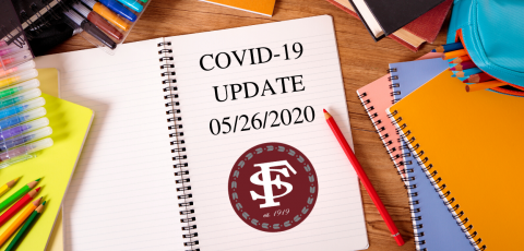 """picture of a desk with a notebook in the middle that says """"COVID19 Update 05/26/2020""""  with the FSCC symbol below it"""