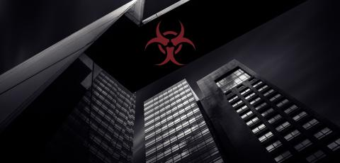 black and white photo of three buildings with a red bio-hazard sign in the middle