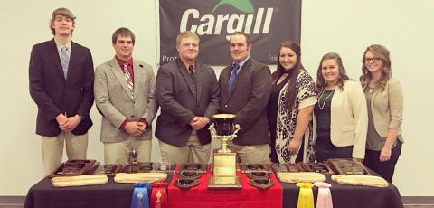 Six students and their coach standing behind a display of their trophies.