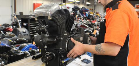 Student standing in front of a motorcycle motor repairing it.