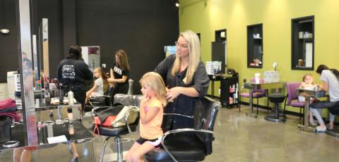 picture of a child getting their hair done by a FSCC cosmetology instructor