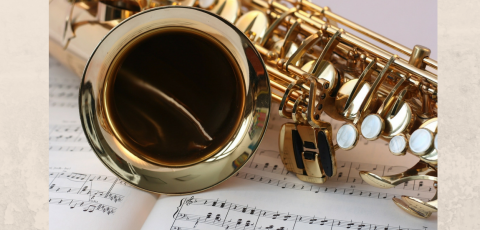 A saxophone laying on an open music book.