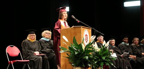 A young female graduate giving a speech while faculty and staff members sit behind her.