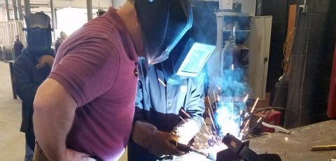 A student welding while an instructor watches closely.