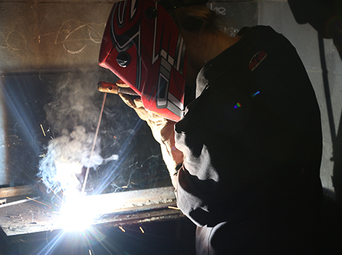 A student with a welding helmet on welding metal.