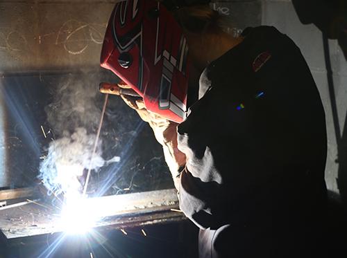 A student with a welding helmet on welding metal.