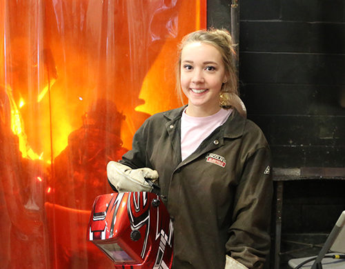 A Welding student wearing her protective gear and smiling for the camera as her colleagues work in the background.