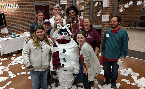 Several students posing with a snowman that they created out of toilet paper.